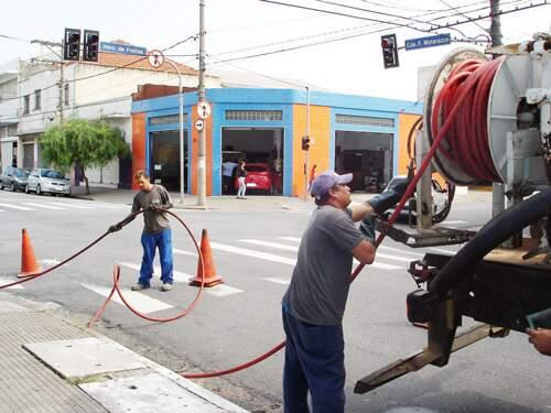 Profissionais aplicam jato de água de alta pressão abastecido por caminhão-pipa