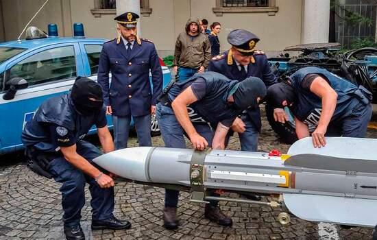 Policiais manejam míssil usado para derrubar aviões apreendido durante a operação