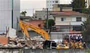 Segundo os bombeiros, trator executava serviço de demolição de um estacionamento quando colidiu com edificação, que caiu sobre os trabalhadores - Continue lendo